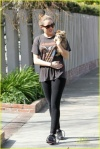 Miley Cyrus, with her hair in a bun and wearing Nike trainers, shows off her adorable dog outside of her home in Toluca Lake